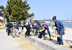 遊歩道に積もった砂を除去する参加者=唐津市西の浜