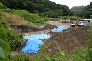 遺体が遺棄された残土処理場。黄色いテープで囲われた場所から発見された。右上に見えるのは長崎自動車道=26日午後、佐賀市久保泉町川久保 編注