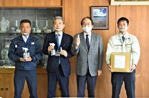 伊万里市に透明マスクや消毒液を寄贈した亀栄グループの前田省吾社長(左から2人目)=市役所