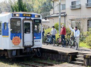 マウンテンバイクとともに乗ってきた列車に手を振る参加者=17日、有田町の蔵宿駅