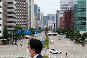 名古屋市の繁華街をマスクを着けて歩く男性。緊急事態宣言に追加された愛知県の新型コロナウイルス感染者数は初めて600人を超え、2日連続で過去最多を更新した=12日午後