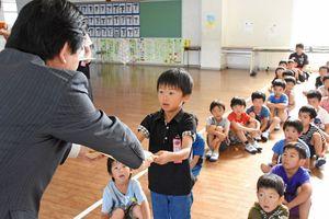 松田一也町長から本を受け取る児童の代表=基山町の若基小