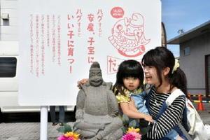 お披露目された「だっこえびす」と触れ合う親子=佐賀市のJA佐賀市中央多布施支店