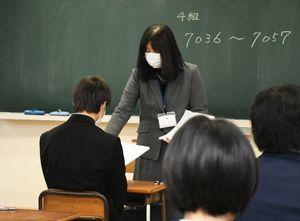 問題用紙を配る学校職員=佐賀市の龍谷高