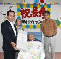市内最高齢の吉村カツミさんに記念品を渡す塚部芳和市長。右は孫の博幸さん、右から3人目は睦子さん=伊万里市
