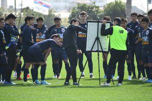 ボードを使い、選手にポジショニングなどを説明する金明輝監督(中央)=沖縄県の読谷村陸上競技場