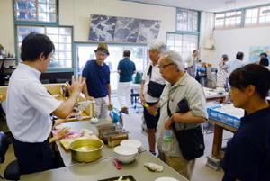 有田焼の製造工程の説明を聞くツアー参加者=有田町の徳永陶磁器