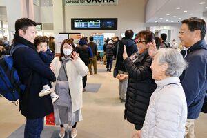 帰省を終え、佐賀空港の出発ロビーで見送りを受ける家族連れ(左側)=佐賀市川副町