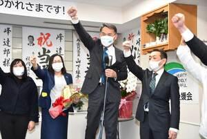 再選が確実になり、拳を突き上げて喜ぶ峰達郎氏(中央)=31日午後10時29分、唐津市新興町の事務所