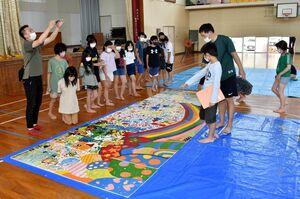 完成した絵を並べる6年生。写真左端が片桐さん=伊万里市の立花小体育館