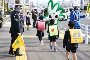 交通安全指導員らに見守られ、通学する新1年生ら=佐賀市の本庄小前