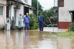 大雨の影響で道が冠水し、立ち尽くす消防団員ら=6日午前9時20分、熊本県津奈木町