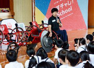 レース用車いすの構造を紹介する永尾さん=鹿島市の北鹿島小学校