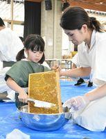 包丁で丁寧に蜜蝋をそぎ落とす子どもと見守る保護者=吉野ケ里歴史公園