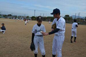 NTT西日本の選手(右)からボールの握り方などを学ぶ少年野球の選手=唐津市の松浦河畔公園野球場