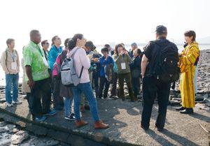 有明海の干満や干潟に住む生物について説明を受ける参加者たち=鹿島市の肥前鹿島干潟