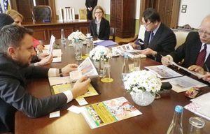 ボスニア・ヘルツェゴビナをイメージした着物のデザイン資料を見るスカーカ市長(左)。右端は伊藤嘉一さん、隣は坂本秀之・日本大使=サラエボ市庁舎