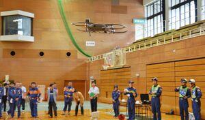 隊員たちの操作訓練で飛行するドローン=唐津市の市文化体育館