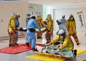 負傷者の重症度によって搬送の優先順位を決める「トリアージ」で救護にあたる消防署員ら=佐賀市川副町の佐賀空港