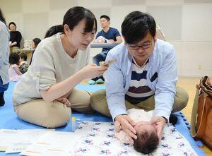 赤ちゃんへのベビーマッサージに挑戦する夫婦=佐賀市のアバンセ