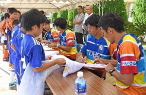 サッカー教室終了後、プレゼントしたユニホームにサインを書く九州レジェンズの講師陣