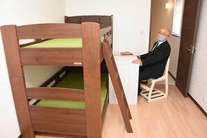 シェルターで子どもが暮らす部屋。ベッドの配置や机の使い心地などを確かめる桑原宏樹施設長=佐賀市内