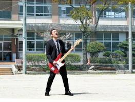 母校・鍋島中学校の校庭でミュージックビデオの撮影に臨むはなわさん=佐賀市