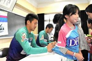 授業終了後、児童のレプリカユニホームにサインする豊田陽平選手(左)。奥は富山貴光選手=伊万里市の黒川小学校