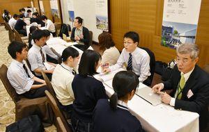 高校生に学校生活や卒業後の進路などを熱心に説明する学校の担当者(右)ら=佐賀市のホテルマリターレ創世
