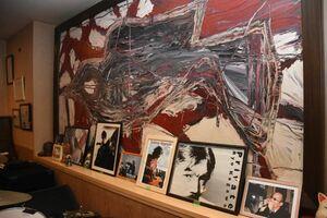 リキさんの写真(右から5枚目)と、リキハウスに出演し亡くなったミュージシャンたちの写真やポスター。絵画は黒田征太郎さんがリキさんと作家の中上健次さんの鎮魂のため描いた作品