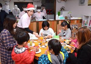 サンタクロースの帽子をかぶった佐賀農業高食品科学科の生徒が運んできたケーキやジュースに喜ぶ子どもたち=江北町の貸しスペース「おへそのおへそ」