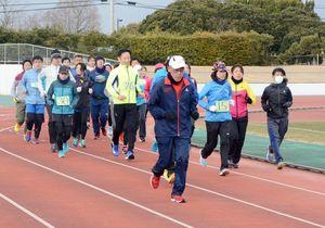 ランニングドリーマー佐賀の江口達也さんの指導を受けながら、コースを周回する市民ランナーたち=佐賀市の県総合運動場
