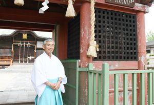国重要文化財「朱塗りの楼門」の前に立つ、宮司の中村良信さん=佐賀市の与賀神社