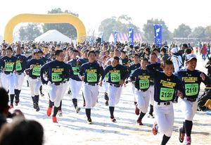 雪が残ったコースを一斉にスタートを切る4キロのランナーたち=吉野ケ里歴史公園