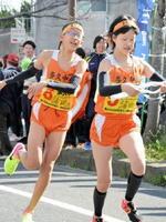 多久市の諸田雄生(左)からたすきを受け取る姉の来奈=21ー22区中継所