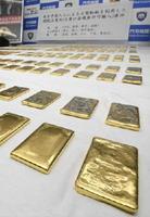 門司税関で報道陣に公開された、押収された金塊。刻印が消されたような跡もあった=2日午後、北九州市