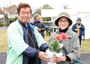 来場2万5千人の記念にダリアを受け取った鬼木喜久子さん(右)。左は出店者会の栗山大完会長=吉野ケ里歴史公園臨時駐車場