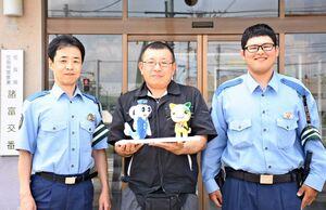贈った人形を持つ浅川さん(中央)と佐賀南署の江里口真さん(左)と山田睦巳さん=佐賀市の諸富交番