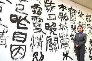 卒業書作展を開く藤原朱里さんと大作「送遠」=佐賀県立美術館