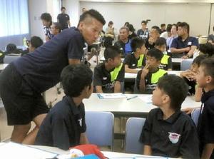 磯崎敬太コーチ(左)と語り合う読谷村U-12の選手たち=鳥栖市のベストアメニティスタジアム