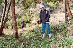 ソロキャンプ場の造成に乗り出す藤瀬吉徳さん、みどりさん夫婦。山の一部を整地する=佐賀市三瀬村