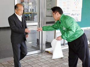 社名変更を知らせるティッシュを配る大樹生命の社員ら=佐賀市のJR佐賀駅前
