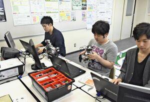 ロボットの調整やプログラミングをするメンバーたち=唐津市松南町の唐津ビジネスカレッジ