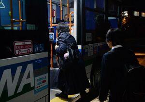 まだ夜が明けていない早朝から通学のためにバスへ乗り込む高校生=12月下旬、佐賀市富士町の「古湯温泉」バス停