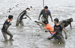 干潟での〝泥合戦〟で泥まみれになりながら、笑顔で交流を深めた太良高校と台湾の高校生たち=鹿島市の七浦海浜スポーツ公園