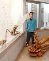 生き物をかたどった木工作品と太田眞一さん=みやき町の風の館
