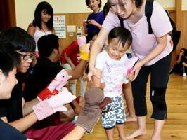 「3びきの子ぶた」の上演後、演じた人形に駆け寄る子ども=南川副公民館