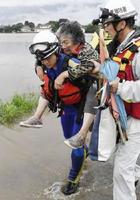 大雨の影響で孤立した地区からボートで救助され、消防隊員に背負われる女性=6日午前7時12分、福岡県朝倉市