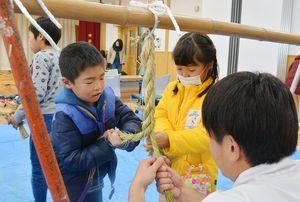 アドバイスを受けながらしめ縄づくりに挑戦する児童たち=佐賀市の若楠公民館