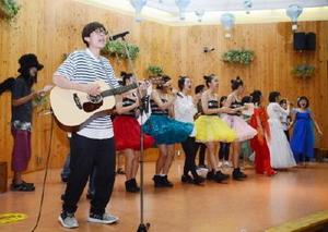18日に行われた100回目の「音楽の時間」で、テーマ曲を歌う出演者たち=佐賀市の656広場